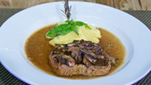 Filete 156, medallón de carne a las finas hierbas con champiñones salteados y puré de papa, bañado en salsa de pimientos